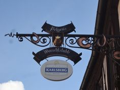This is a unique artistic shop sign for a restaurant called 'Pelgen's Worschtstubb' (Pelgens Sausage Parlor). It is located at the streeet called 'Hintergasse' in the old town in Neustadt/Weinstraße, Germany, Rheinland-Pfalz.