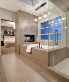 Contemporary Master Bathroom with Double-sided Gas Fireplace, Master bathroom, Skylight, frameless showerdoor