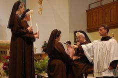 Sister Maria Serra Garcia pronounces her perpetual vows into the hands of Mother Shaun Vergauwen, Mother General, as Sister Sarah Doser (left) and Sister Mary Richards stand as witnesses, and Brother Leo Maneri holds the microphone.