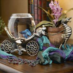 "Hand-blown glass beta bowl on a sea life-inspired chariot stand in Victorian brass. Features a battery-operated LED lighting system.  Product: Beta bowlConstruction Material: Glass and brassColor: BrassFeatures: Hand-blown glassDimensions: 7.25"" H x 16.25"" W x 5"" D"