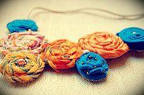 Collar babero hecho en tela y decorado con abalorios cosidos uno a uno y a mano.