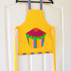 """Kids/Toddlers Cupcake Apron, yellow childs polka dot kitchen play art craft apron, girls & boys lined cotton polka dot apron with pretty candy stripes cupcake pocket, toddlers pinny, Cupcake  """"Mmmmm yummy Cupcakes !""""  Spoil your budding chef with these cute Cupcake kid's aprons. These gorgeous and practical bright aprons will delight not only your own little kitchen helper, but their friends will want one too!  Perfect for helping mum bake those delicious cupcakes or as a craft apron for…"""