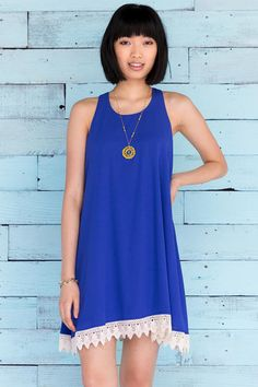 """Ivory crochet trims the bottom of this solid blue shift dress. Wedges & a pendant necklace finish off the look.<br /> <br /> - 35"""" length from shoulder to hem<br /> - 34"""" chest<br /> - 70"""" sweep<br /> - measured from a size small<br /> <br /> - 100% Polyester<br /> - Hand Wash<br /> - Imported"""