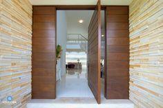 Este hall de entrada conta com revestimento de pedra palito nas paredes, porcelanato no piso e porta pivotante em madeira.