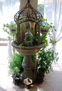 love this vignette.  Birdbath with a stylized metal cage/gazebo flanked by greenery