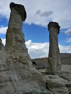 Two tall, thick hoodoos, topped by purple caprocks; Wahweap Creek, Utah