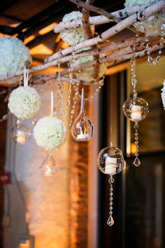 Reception Decor - hanging birch fixture with floral poms and candle votives - an absolute eye-catcher! See more of the wedding on SMP: http://www.StyleMePretty.com/midwest-weddings/2013/12/26/fultons-on-the-river-wedding/ Ann & Kam Photography & Cinema