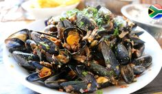 The thought of mussels in white wine just screams of a South African summer, doesn't it? There's certainly that summery feeling in the air and to celebrate the change of the cooler months to our sizzling festive South African summer season, we're going to share not one, but two delectable South African seafood recipes starring the main event: mussels in white wine! #Mussels #SouthAfrican #Recipe Mussels White Wine, Seafood Recipes, African, Vegetables, Ethnic Recipes, Festive, Change, Summer, Environment