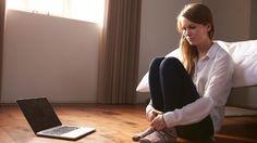 Frau sitzt unglücklich vor ihrem Bett auf dem Boden.  (Quelle: Thinkstock by Getty-Images)