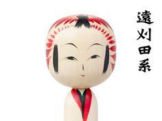 遠刈田温泉を中心として生まれた系統。直胴に大きめの頭のシンプルな姿です。顔は上下のまぶたが描かれ、鼻は割れ鼻。胴体には、菊や梅、桜などをモチーフとした絵柄が施されることが多く、頭頂には赤い放射状の手絡(髪飾り)模様、さらに額から頬にかけて赤い花弁模様が描かれます。 / こけしいろいろ | 手とてとテ -仙台・宮城のてしごとたち-