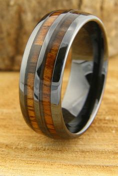 By far one of the most unique mens wedding band. The ring is called The Vintage Barrel Ring. Hence, that is where the design came from for this amazing wood wedding band. This makes a perfect mens wedding band. It is crafted out of black high tech ceramic and genuine koa wood. The ring is 100% waterproof and very durable. It comes in widths 6mm and 8mm.