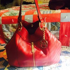 Authentic Michael Kors purse!! Reserved This is absolutely stunning!! Red leather with gold hardware! You can wear it different ways with the sides zipped to make it like a bucket style or unzipped to make bigger like a tote. It's in excellent condition!! Just beautiful. Trade value 275 Michael Kors Bags