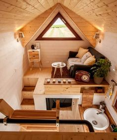 Like this cozy little living room nook. Large triangle windows on either side of the tiny house allow for good cross-ventilation.