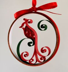 This ornament shows a heavily stylized cardinal perched on a dark green curl. The ring is lined with snowy white. Each ornament is just over two