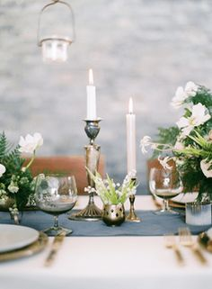 White flowers, silver candlesticks, gold flatware, and a dusty blue table runner. #winter #wedding #tablescape