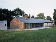 Material Palette: red brick, grey standing seam metal roof, steel windows, vertical wood siding
