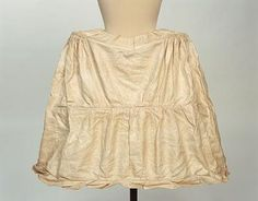 c1765-75 | Manchester Galleries | Accession: 1953.71/3 | Made from cane hoops, covered in linen, sewn into linen petticoat. Open down back with a drawstring at the waist. Top hoop shaped to slight V at centre front. Four strips of padding over each hip above first hoop. Linen tape ties at back level with top and middle hoops. Back and side fronts of middle and bottom hoops connected with linen tape braces inside. | Dimensions: Length (height) 66 cm, circumference (bottom hoops) (width) 184.2