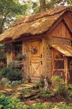 wow!! LOOK at this adorable thatch roofed garden shed!!! lovely stone path, plantings, window boxes, and ground cover tOO.....