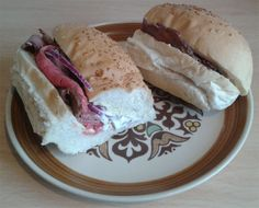 A rare roast beef with wasabi mayonnaise and red onion sandwich.
