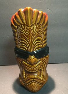 "The Tikinator Tiki Mug Designed by Rick Rietveld For Tiki Farm in 2005. This large mug was designed by popular surf artist Rick Rietveld for Tiki Farm. The mug features a large tiki head with Maori-style markings, wearing sunglasses. ""The Tikinator"" is in raised letters down the back of the mug."