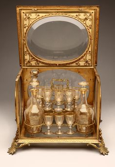 A French gilt-bronze tantalus, Probably 19th century, the rectangular double-hinged top centered by a beveled glazed panel, over similar sides opening to a fitted interior with 3 decanters and 13 cordial glasses, decorated with gilt bands, all on foliate-cast feet,