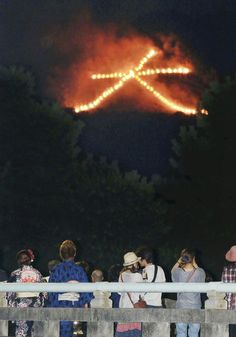"August 16 is the end of the Obon holiday, when the ancestors visit the living. They are guided on their way by the fires on the mountains around Kyoto. Here people are looking at a fire in the shape of the Chinese character ""dai"" (big). You can see three of the fires from Ebisu's Kyoto, and you can see the fire in the photo from the top of the hill upon which the house sits (Yoshidayama)."
