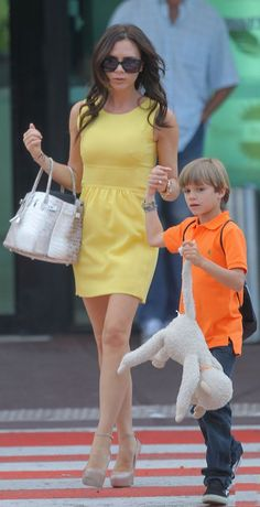 Victoria Beckham shows off her longer locks as she arrives at Cannes airport with her son Romeo Beckham in France. June, 2010