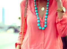 Coral shirt, teal statement necklace and golden watch.