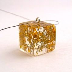 I just love this - a yellow resin pendant with pressed baby's breath. It is so simple and refreshing. by SpottedDogAsheville at Etsy.