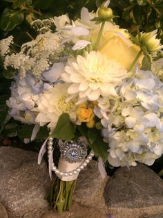 A vintage inspired bouquet of blue and white hydrangea, white dahlias, yellow garden roses, spray roses, and queen anne's lace. all wrapped in satin, lace, draped in pearls and pinned with a brooch. www.rsvpfloral.com