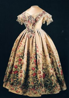 White French silk embroidered dress thought to have been worn by Queen Victoria during her state visit to Paris in 1855. The dress is decorated with colourful flowers, mostly geraniums.