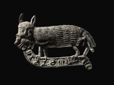 Badge; lead alloy; cat with mouse in mouth, standing upon inscribed scroll.