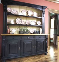 A freestanding hutch replaces an old built-in cabinet in this kitchen. It displays fine china and other personal heirlooms with an open storage space above and closed cabinetry below, with a dark stain that provides a perfect contrast to the crimson walls. The maple-colored ledge brings continuity to the kitchen by matching the floors and other woodwork.
