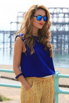blue sleeveless tops, printed yellow pants and mirror glasses.
