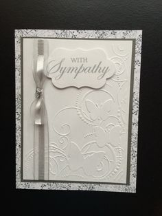 "Sympathy card using Spellbinders Petite Labels One die D-Lites and ""With Sympathy""clear stamp. 5x6.5"" pre-made white card was layered with gray card stock and white card stock embossed with Darice - Butterfly Swirls embossing folder.  Gray sheer and satin ribbon was used along the side of the card and tucked under the white card stock layer. Created by: Melanie Weise"