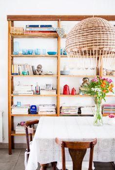 Sinfonía en blanco. Protagonista en todos los ambientes, en el comedor se combina con la estantería angosta, que pertenecía a una antigua juguetería; la lámpara de ratán y el mantel de hule, comprado en Roma, que parece de encaje de Bruselas