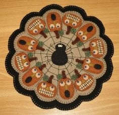 """Irresistable little pumpkins with frightened faces adorn the scalloped edge of this fun Halloween candle mat! Create this penny rug/candle mat pattern using wool or wool felt in beautiful fall colors. A great centerpiece for your Autumn table! Finished Size: 14"""". Skill Level: Advanced Beginner. Halloween Applique, Halloween Patterns, Halloween Candles, Fall Halloween, Easy Quilt Patterns, Penny Rugs, Blanket Stitch, Spring Blossom, Wool Applique"""