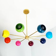 "The Arcenciel Chandelier is a playful chandelier with Mid Century Modern vibes.  French for ""rainbow,"" The Arcenciel Chandelier has six eyeball shades in six different colors to mimic a color wheel or rainbow.  This chandelier goes great with our other Loa fixtures, including sconces.  This fixture would be a fun accent or take the spotlight in a modern nursery, colorful childrens bedroom/playroom, add a little fun into an otherwise boring office, or even jazz up a sleek, white..."