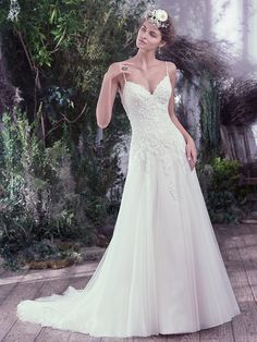 Maggie Sottero - BETH, Delicate beaded spaghetti straps and a feminine V-neckline add ethereal touches to this A-line wedding dress. Swarovski crystals and beading adorn a fitted lace bodice before falling into a weightless tulle skirt. Finished with covered buttons over zipper and inner corset closure.