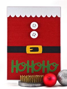 Say Merry Christmas with this funny, festive Santa suit card. When Santa dons his suit, it definitely accentuates his belly. Although his is depicted as being quite round, this card isn't quite as fluffy. It does have some dimension though from the white buttons stitched on with embroidery floss. #thecardkiosk