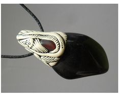 Apache Tear Pendant with Garnet inset. Apache Tears: Properties: The stones are said to bring good luck to those possessing them. Black obsidian is a powerful Meditation stone. The purpose of this gemstone is to bring to light that which is hidden from the conscious mind. It dissolves suppressed negative patterns and purifies them. It can create a somewhat radical behavior change as new positive attitudes replace old, negative, egocentric patterns.