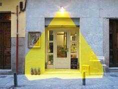 #Street #mkguerrila  INSTALACIÓNEN (Fos)  MADRID   La fachada del restaurante vegano Rayen en la calle Lope de Vega en Madrid ha sido iluminada por 4 días y noches por más de 250 ml de cinta amarilla, los artículos de decoración han sido pintados, piñas y … una lámpara. Un juego visual entre la perspectiva y el volumen de color que ganó las miradas de los que por ahí pasaban.