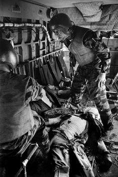 Exhausted by the strain, Farley stands over Magel's body while Hoilien (back to camera) tries to comfort Owens. Larry Burrows Vietnam