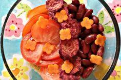 Salade de quinoa vide-frigo avec des quartiers de tomate, croustilles de betterave, haricots et carottes en fleur.
