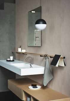 String Lights by Michael Anastassiades complement the modern vibe in this bathroom with a neutral color scheme and wood accents.