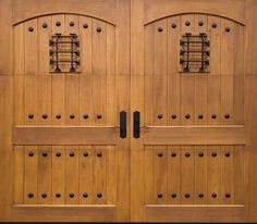 The perfect finishing touch on any Spanish/Mediterranean style home. Clopay Reserve Collection custom wood carriage style garage door with grooved, arched panel design, decorative wrought clavos and speak-easy. www.clopay.com