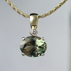 Rare 2.58ct green oval cut Oregon Sunstone set in 14k yellow gold with diamond accent.    620-008