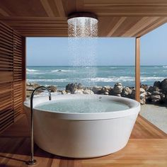 Gorgeous Zucchetti Kos Geo 180 freestanding bathtub in outdoor wooden bathroom with amazing ocean view. Beautify Your Modern Bathroom Design With These Modern Zucchetti Faucets, Showers, And Tubs