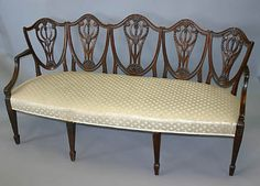 Rare, George III period, chair-back settee. In mahogany with slightly curved, five shield-form backrest, each with bellflower and white carved splat continuing to downward sloping arm rests and supports, above a padded seat, raised on rosette capped fluted straight tapering legs ending in spade feet. 18th century.