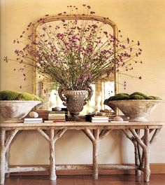 Faux bois console table with flower arrangement and planters filled with moss